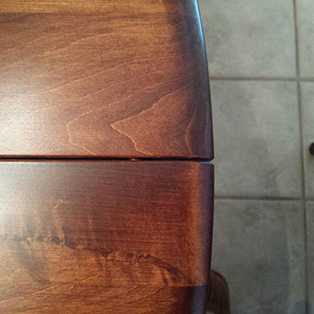 This photo is the result of too low humidity, creating a gap at the ends of the joints. If the humidity is too high, the table will gap at the center of the joints. [Amish Direct Furniture]